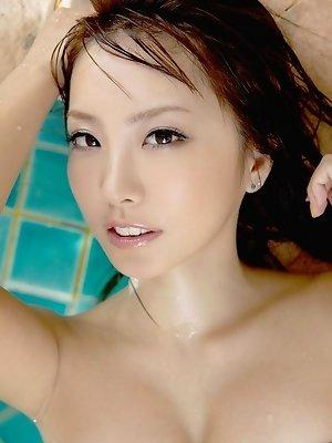 Sensual gravure idol babe enchants in her slinky wet shirt
